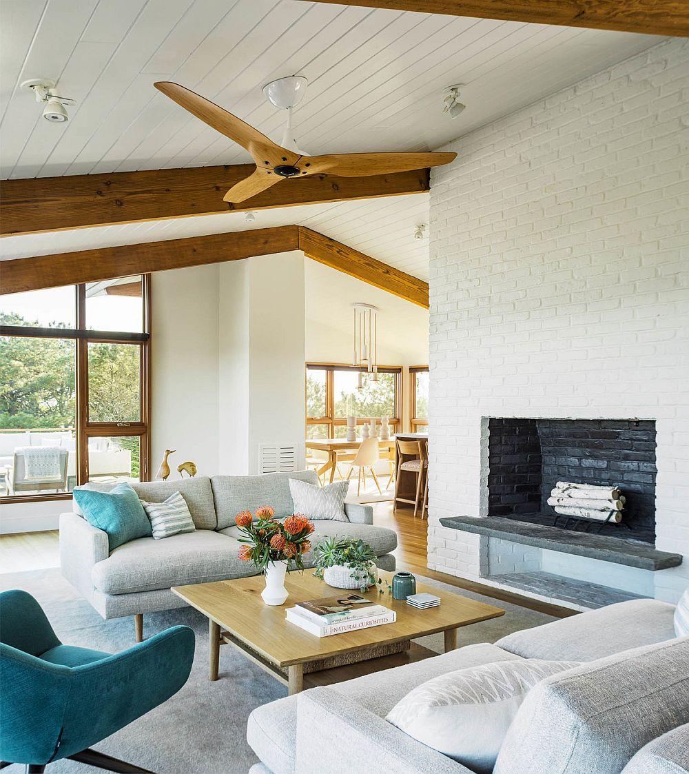 Spațiul camerei de zi este marcat prin ferestre generoase, de arhitectura conferită de planul acoperișului, dar și prin prezența șemineului ce delimitează încăperea de bucătărie.