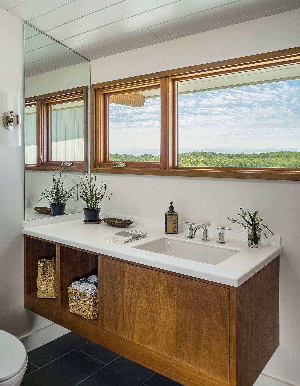 Ce faci când în baie simgura modalitate de a amplsa lavoarele este sub ferestre? Sacrifici ferestrele pentru oglindă? Nu! Poți pune oglinda în lateral. Oricum la un asemenea peisaj mai degrabă îți odihnești privirea admirând natura decât propriul chip.
