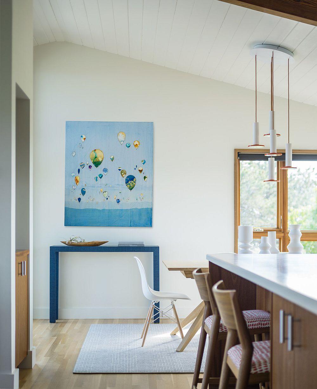 Tabloul și masa consolă în nuanțe albastre sunt elemente cromatice de contrast cu textura lemnului și cu albul pereților, o combinație ce sugerează stilul marin. Cele două elemente sunt prezente la granița dintre bucătărie și living. Practic, ele fac legătura cu livingul.