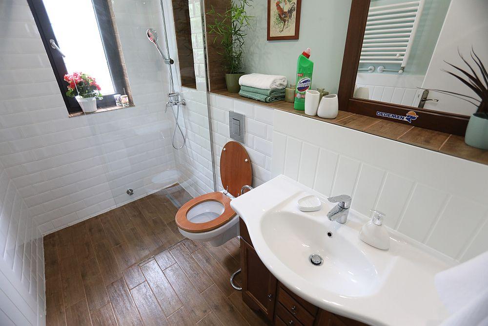 Baia după renovarea făcută de către echipa Visuri la cheie. Baia a fost amenajată după proiectul meu. Am prevăzut un duș cu rigolă îngropată, separat cu panou de sticlă, astfel încât Iulia să poată accesa ușor acest spațiu. La nevoie poate folosi un scaun, dacă nu poate sta în picioare la duș, dar de asemenea se poate sprijini de suportul dușului, precum și de glaful ferestrei. Poziția vasului wc a fost schimbată pentru a exista sprijin pe mobilă, iar înălțimea vasului a fost reglată după cum și-a dorit Iulia.