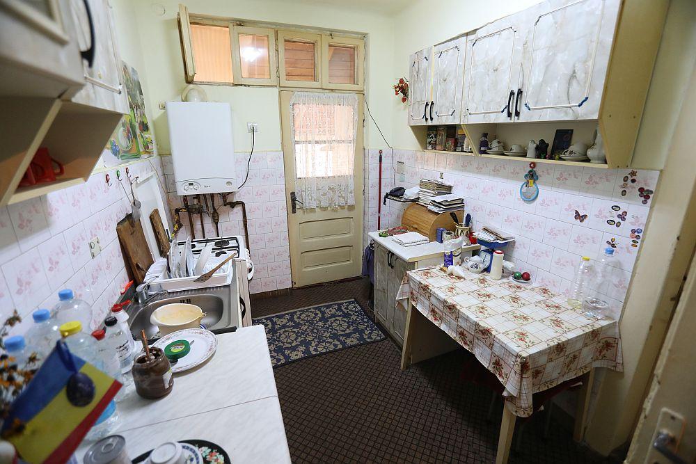 Bucătăria înainte de renovarea făcută de către echipa Visuri la cheie. Spațiul era mic și unul de trecre, având în vedere că pe aici se făcea intrarea ăn casă. În saptele zidului pe care este sprijinită masa se afla cămara.