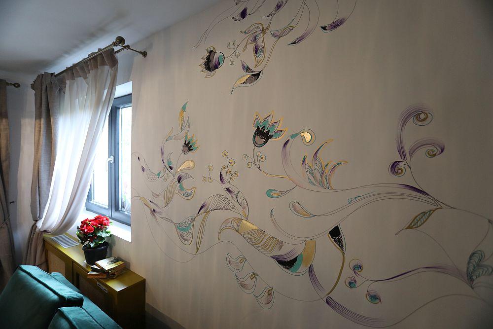 Peretele din living a fost personalizat de către Cristina Joia cu desene și aplicații de foiță de aur, la fel ca și masa din living.