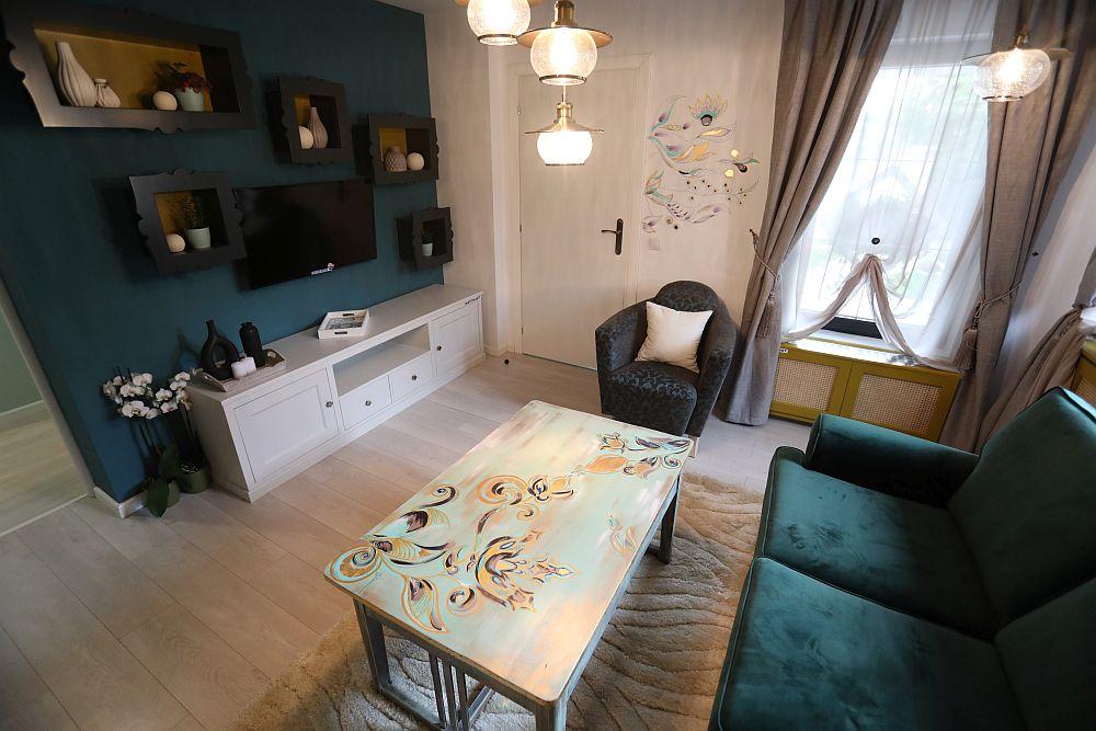 După ușa de la intrarea în living este organizată zona de tv. Livingul este amenajat după proiectul colegei noastre Cristina Joia. Mobila este realizată pe comandă la Martplast după proiectul ei, televizorul și decorațiunile sunt de la Dedeman.