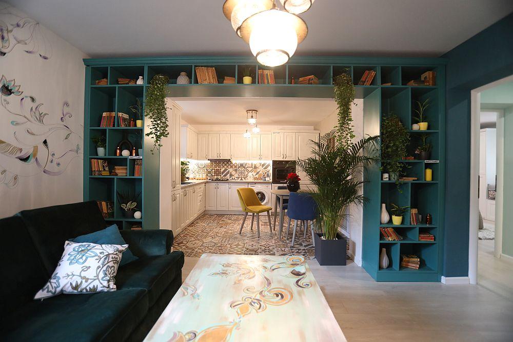 Livingul după renovarea făcută de către echipa Visuri la cheie. Livingul a fost amenajat după proiectul colegei noastre Cristina Joia, care a prevăzut încadrarea golului dintre living și bucătărie cu o bibliotecă comandată în aceeași nuanță ca și cea a peretelui. Mobila a fost realizată la Martplast, plantele, decorațiuni și corpurile de iluminat sunt de la Dedeman.