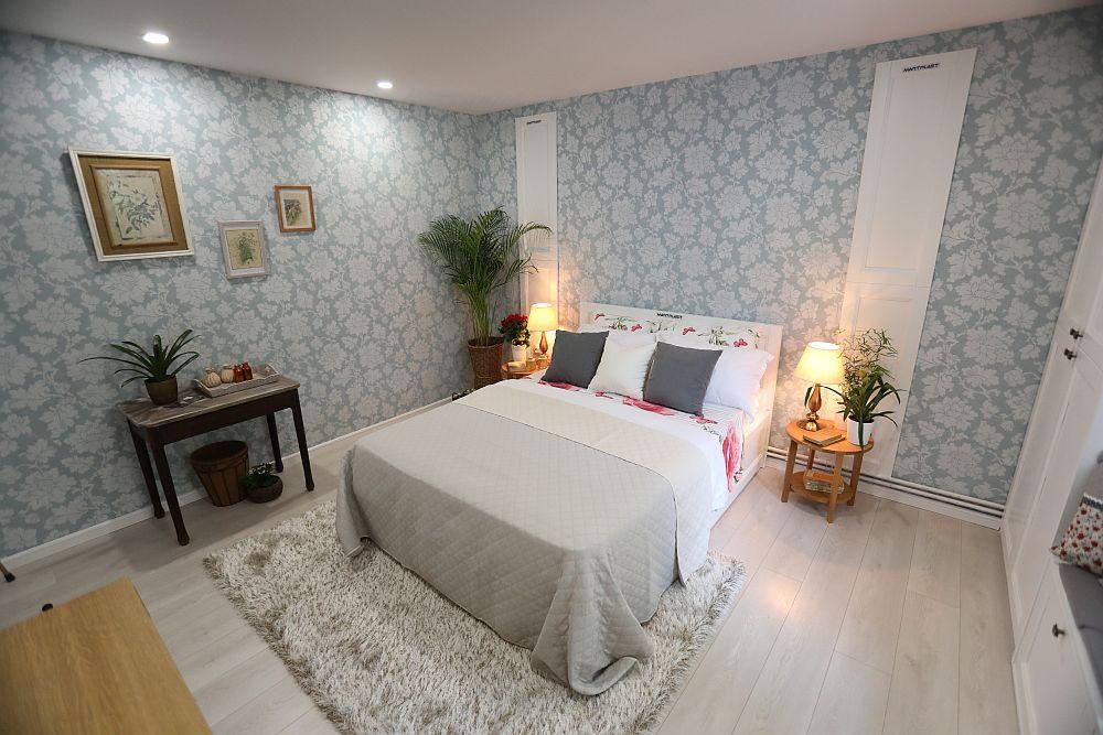 Camera după renovarea făcută de către echipa Visuri la cheie. Dormitorul mamei a fost amenajat după proiectul gândit de mine. Am prevăut ca pereții să fie îmbrăcați cu tapet (de la Dedeman), mobila a fost realizată la Martplast, iar măsuța este păstrată din ceea ce avea familia. Tablourile decorative sunt contribuția mea. Măsuțele pe post de noptiere sunt realizate tot la Martplast. Decorațiunile textile sunt de la Dedeman, la fel și plantele decorative.