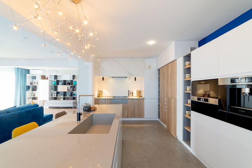 """Ansamblul de mobilier din bucătărie a fost gândit în relație și cu restul ambientului din zona de zi. Deasupra mesei insulă este un corp de iluminat deosebit - modelul """"Universe"""" de la Quasar."""