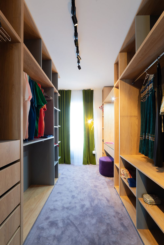Dressingul situat în spatele patului este generos și organizat pentru ambii soți.