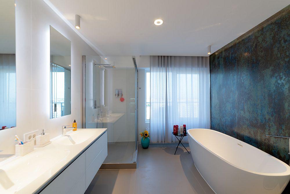 Baia matrimonială are două zone: cea dedicată relaxării cu lavoar și cadă, iar separat zona cu vas de toaletă.