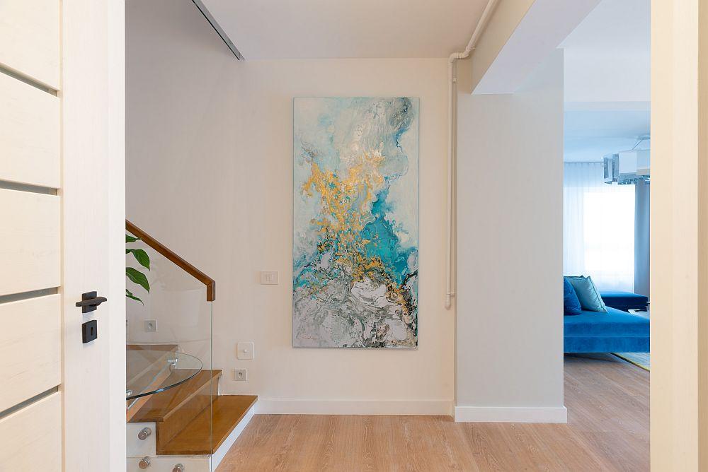 La intrarea în locuință se citește o parte din living, dar te întâmpină un tablou ce vorbește despre cromatica din ambientul zonei de zi.