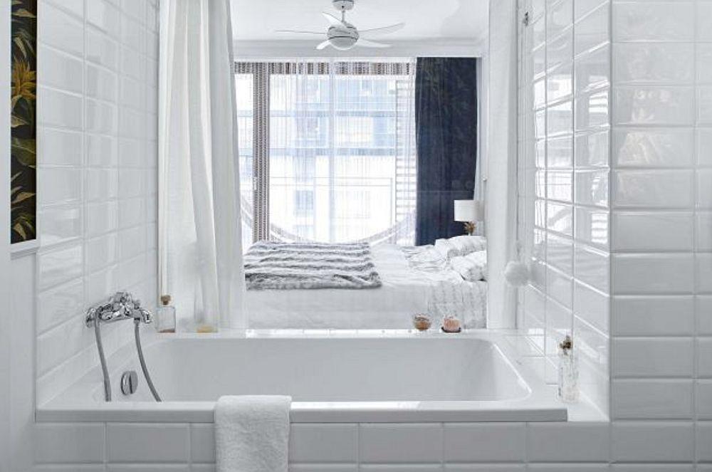 Din baie geamul către dormitorul lasă lumina naturală să pătrundă în spațiul dedicat igienei, ceea ce face ca încăperea să pară mult mai mare decât în realitate.