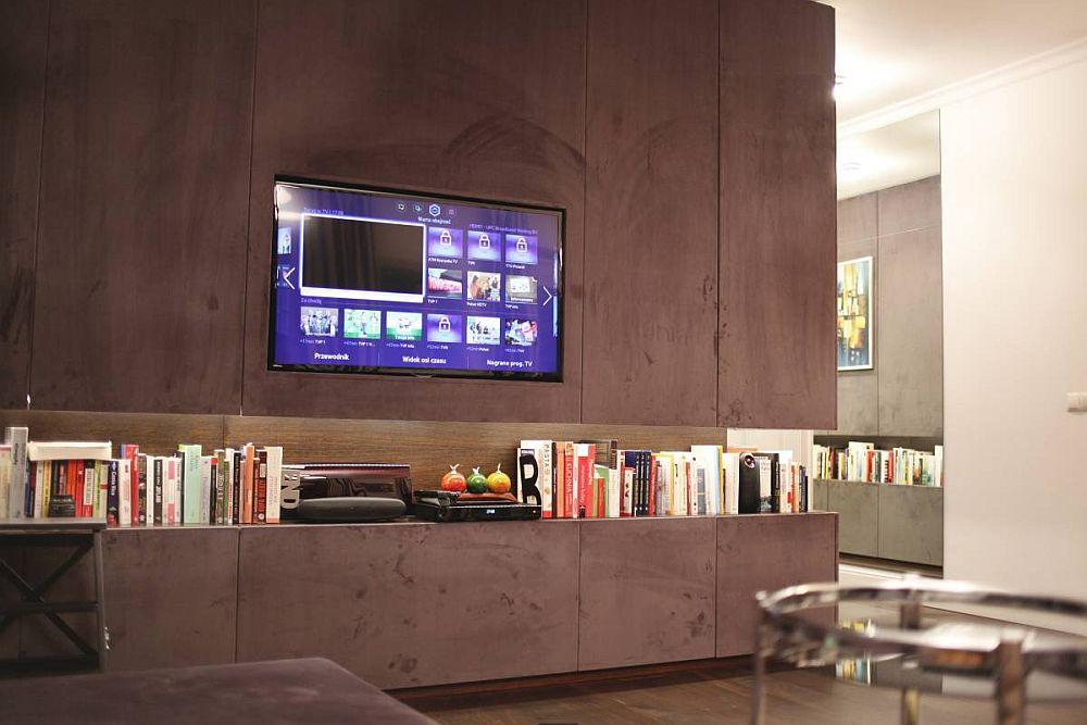 Televizorul este perfect integrat într-una din ușile ansamblului de mobilier. Chiar și spațiul din spatele televizorului poate fi accesat. Imagine captată pe timpul serii când sub influența luminii artificiale calde culorile de la interior par să se schimbe.