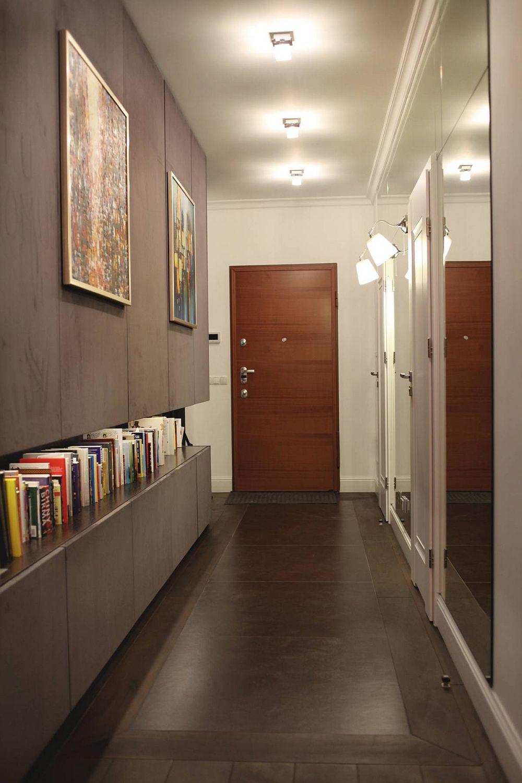 Holul de la intrarea în casă lasă la vedere o parte din ansamblul de dulapuri de pe hol. pardoseala este placată cu plăci mari de gresie încadrate de unele cu textură din lemn. Imaginea aceasta este suprinsă pe timpul serii, când nuanțele de interior se schimbă sub influența luminii artificiale calde.