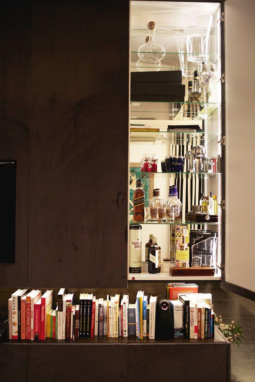 Pe colțul ansamblului de depozitare din living, în spatele uneia dintre uși, este mascată vitrina bar a familiei.