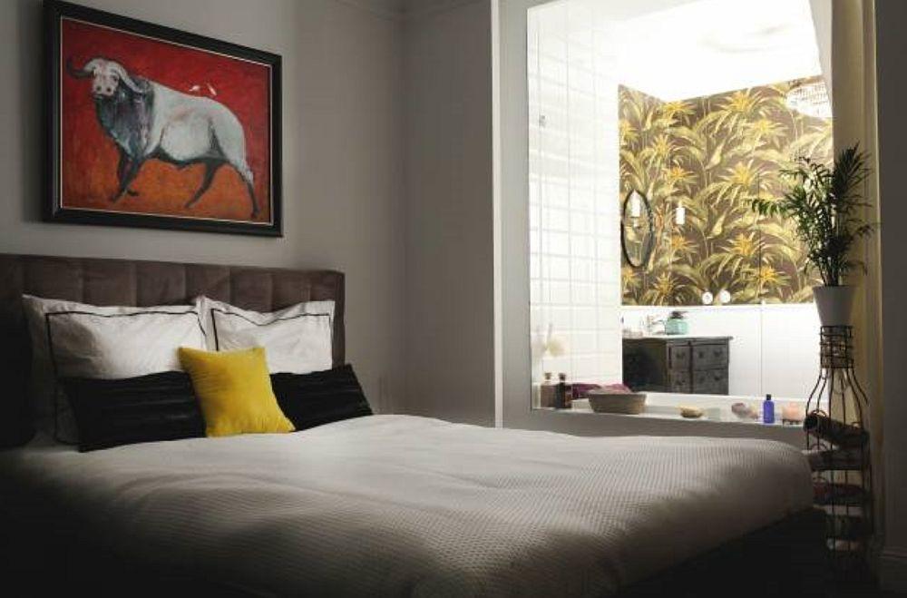 Dormitorul matrimonial este mai special pentru că baia este separată printr-un nou dublu de sticlă. În afara acestui panou este instalat un sistem automatizat de draperie, care poate fi acționat din interiorul băii pentru intimitate. Proprietarii și-au dorit o astfel de soluție pe care au văzut-o într-un hotel din Thailanda, unde s-au simțit foarte bine.