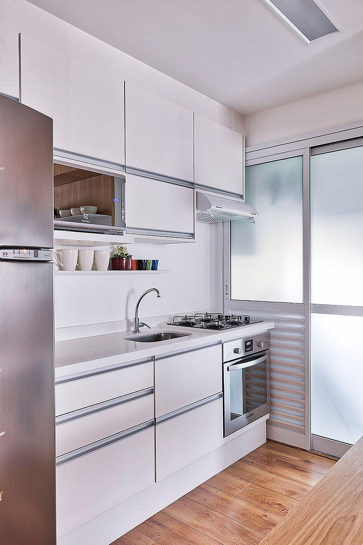 Bucătăria este minimală, mai exact o chicinetă pentru care s-a făcut un compromis major: plita este poziționată lângă chiuvetă. În mod normal nu se face o asemenea alăturare, dar în cazul de față proprietara a spus că nu obișnuiește să gătească acasă și preferă mai mult spațiu de depozitare. Lângă bucătărie, se află un spațiu separat pentru mașina de spălat rufe și lo pentru uscarea hainelor, delimitat printr-o tâmplărie cu geamuri sablate.