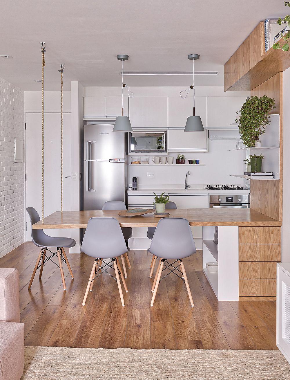 Intrarea în casă coincide cu cea în spațiul bucătăriei deschise către living. Aici se află și masa suspendată într-o parte cu sfori din sisal.