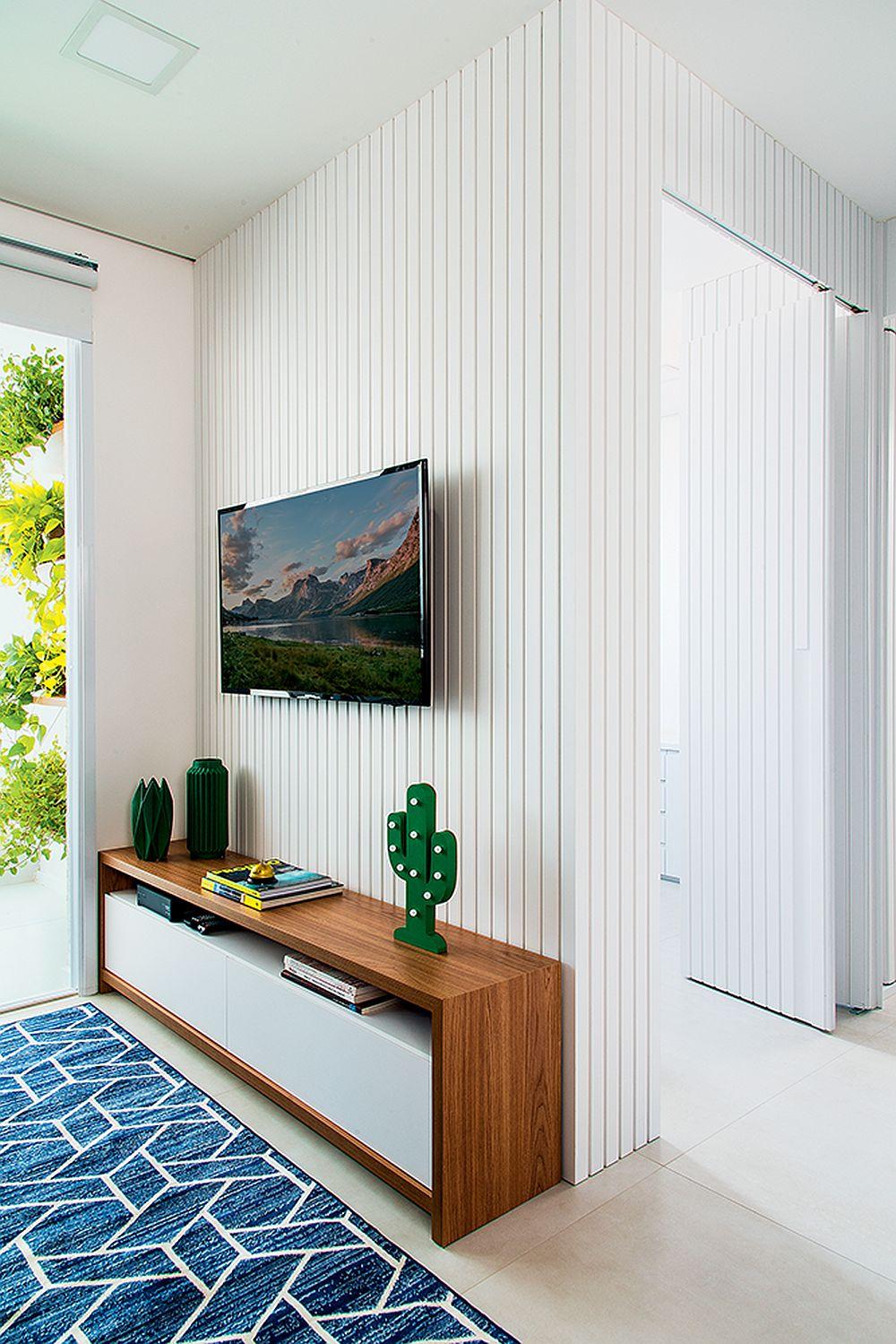 În fața canapelei din living se află comoda pentru tv. Pentru a camufla prezența ușilor din holul deschis al zonei de noapte, arhitecta a prevăzut lambriuri care îmbracă peretele din spatele televizorului, lambriu al cărui desen este continuat mai departe și în hol. Un truc bun pentru a mai estompa din fragmentarea locuinței.