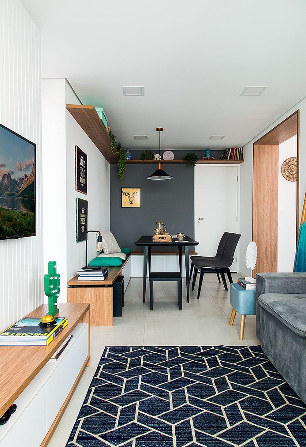 Ușa albă din dreapta este cea de la intrare în locuință. Raftul superior, aproape de tavan oferă loc de depozitare și continua ca și culoare și textură materialul folosit și pentru intradosul golului dinspre bucătărie. Pardoseala este aceeași ca și în bucătărie, dar în zona canapelei aceasta este acoperită cu un covor cu motive geomtrice pentru a creiona o atmosferă mai plăcută, mai caldă. Spațiul fiiind mic, mobilierul pe verticală lipsește, tocmai pentru a nu aglomera spațiul mic și îngust.