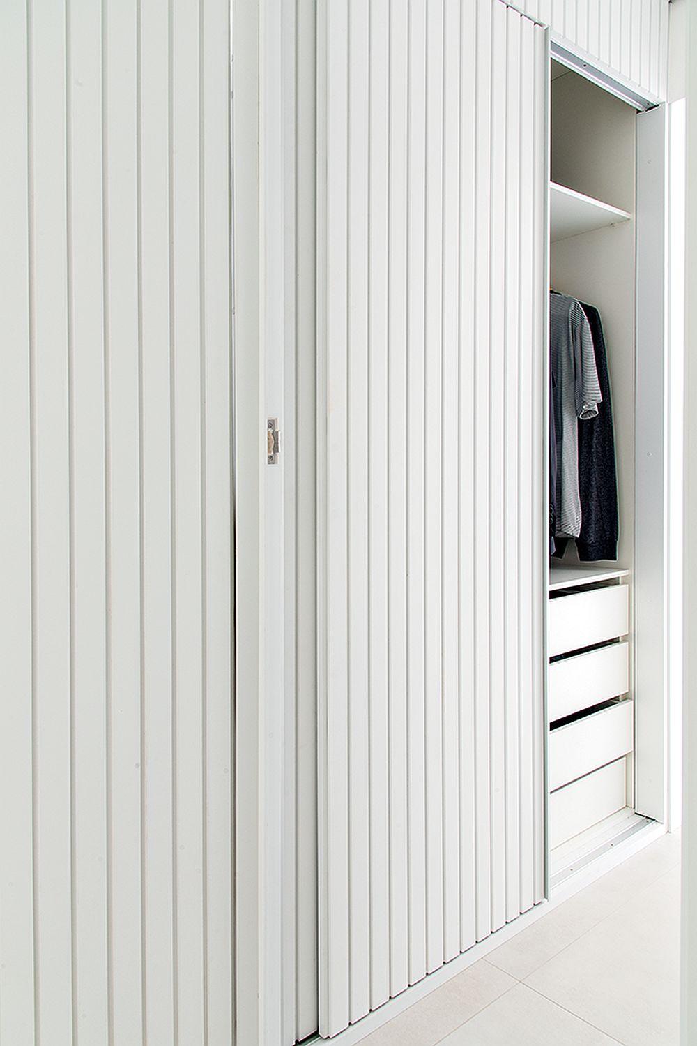 În hol, în spatele finisajului similar cu al lambriurilor este ascuns un dulap cu uși glisante. Acest dulap de pe holul dormitorului este folosit pentru pantofi și pentru haine, preluând și locul de cuier.