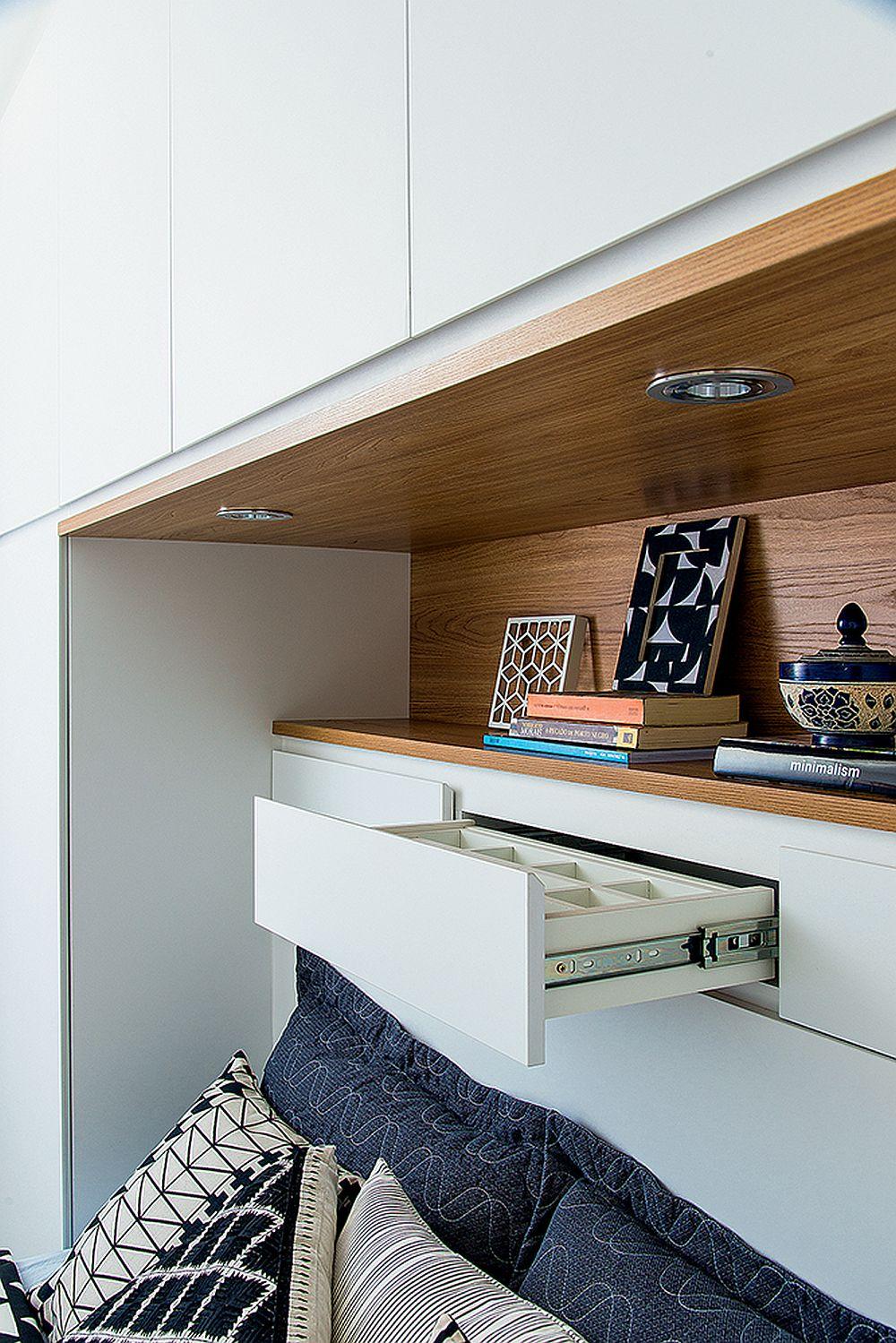 Sertare cu glisiere moderne configurate în tăblia patului sunt compartimentate pentru depozitare de lucruri mici.