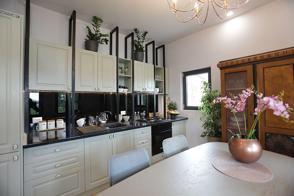 Mobila din bucătărie am gândit-o cu niște elemente verticale care să fie până la nivelul plafonului pentru a armoniza această latură a spațiului cu cea opusă, unde sunt prezente ferestrele înalte.