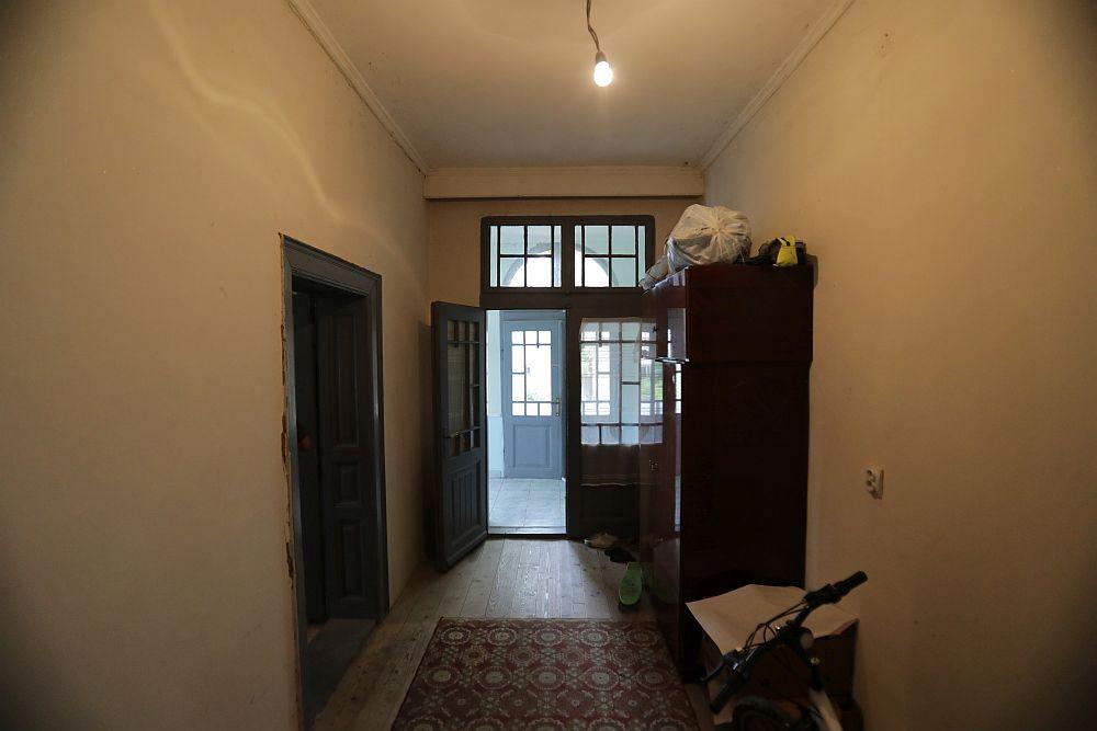Holul înainte de renovare. Se vede și ușa de la intrarea în casă, dar și ușa din stânga care dădea în camera transformată în living. Acum ea este zidită.