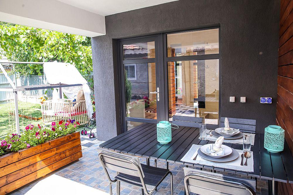 Ciprian a prevăzut o delimitare între terasă și curte prin intermediul unei jardiniere, ale cărei plante colorează totul. De asemenea, mobilierul ales a fost în ton cu tâmplăria, iar textura lemnului adăugă un plus de căldură și familiaritate terasei.