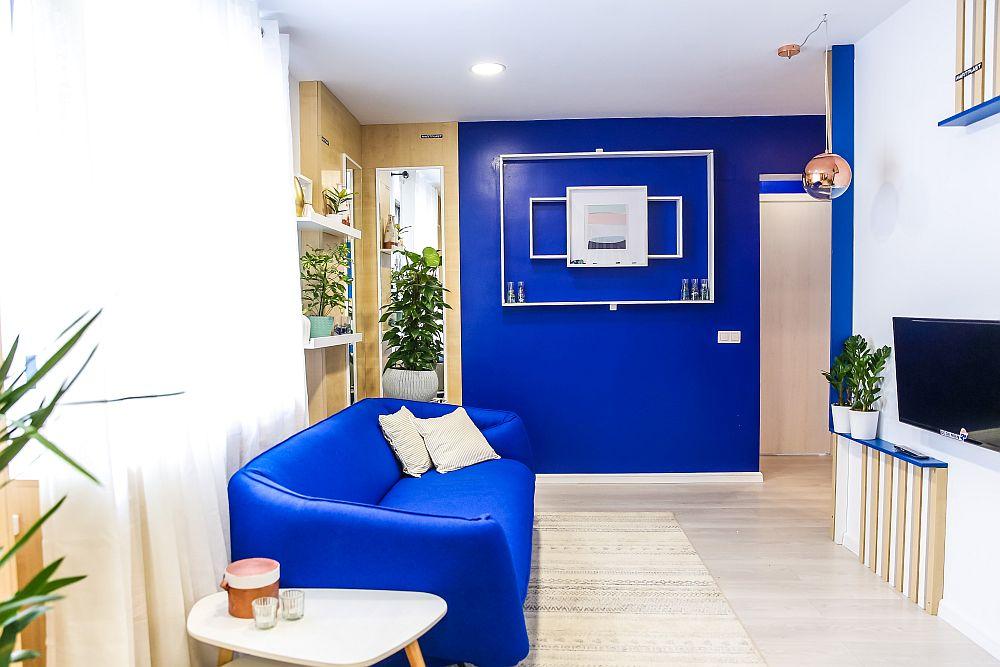 Nuanța albastră este prezentă pe peretele cu ușa dinspre hol pentru a da adâncime camerei. De asemenea, am ales o nuanță de albastru foarte aproape de tapițeria canapelei.