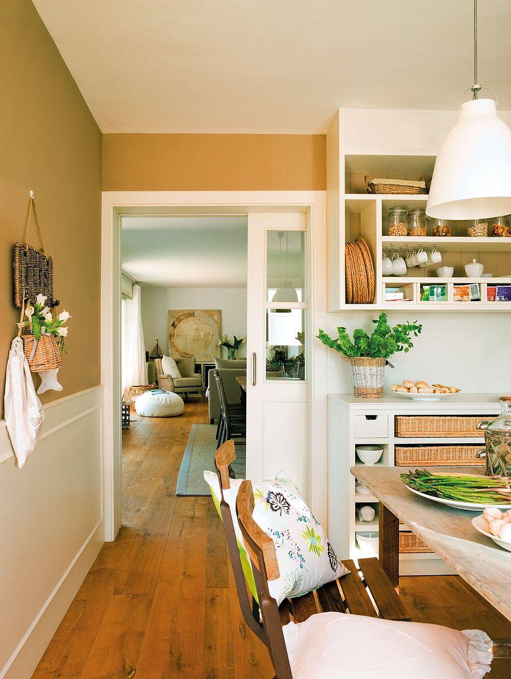 Din bucătărie se accede mai departe înspre living, separarea făcându-se prin intermediul unei uși interioare culisante. Peretele liber, din zona de circulație către grădină este protejat în partea inferioară cu lambriu, al cărui desen este în concordanță cu cel al mobilierului bucătăriei. De remarcat faptul că pardoseala din lemn este aceeași și este se continuă frumos mai departe către living.