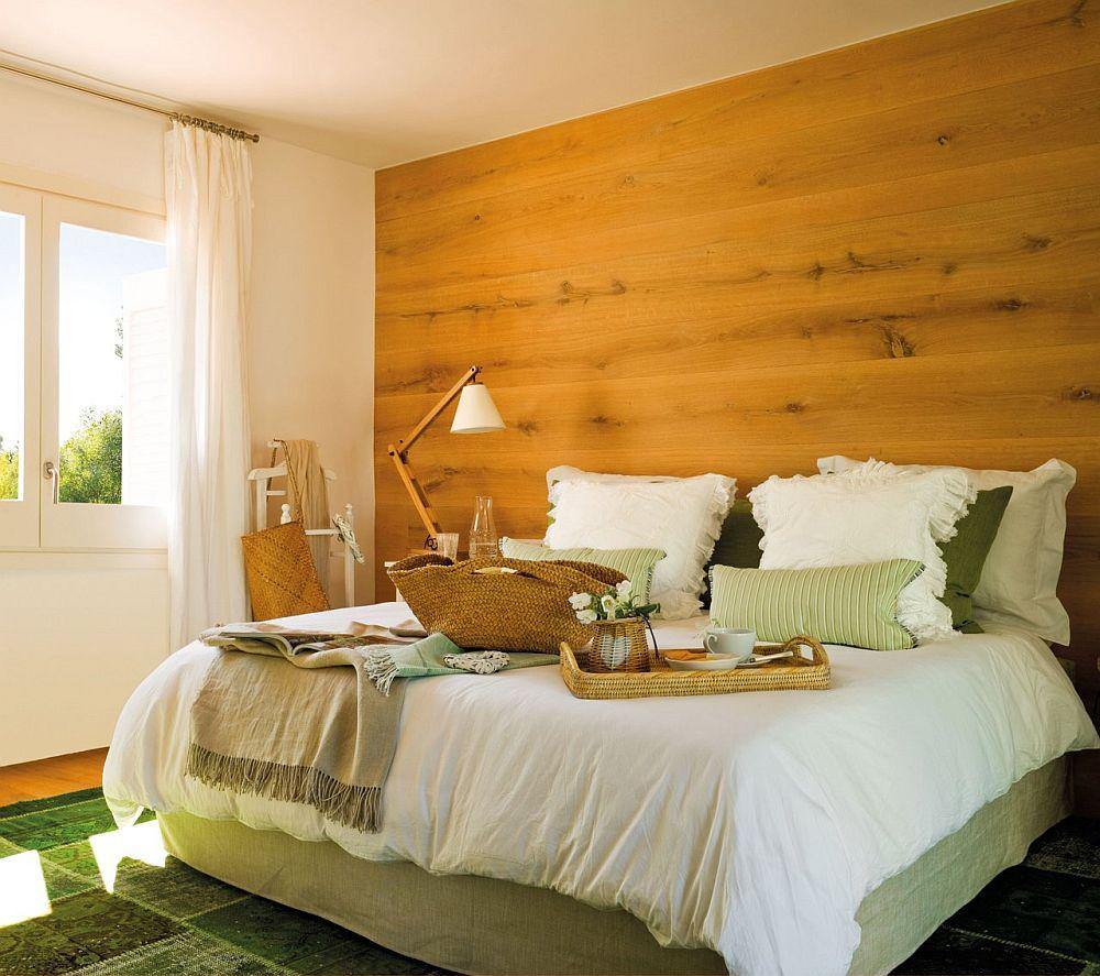 Cu ce se potrivește textura din lemn auriu dacă nu cu verde? O combinație excelentă atunci când vrei să aduci senzața de natură în dormitor. Confortul este subliniat prin patul tapițat și prin lenjeria de pat asortată. Perne multe, dar și perdele bogate, simple albe, care mai sting din prezența dominantă a lemnului.