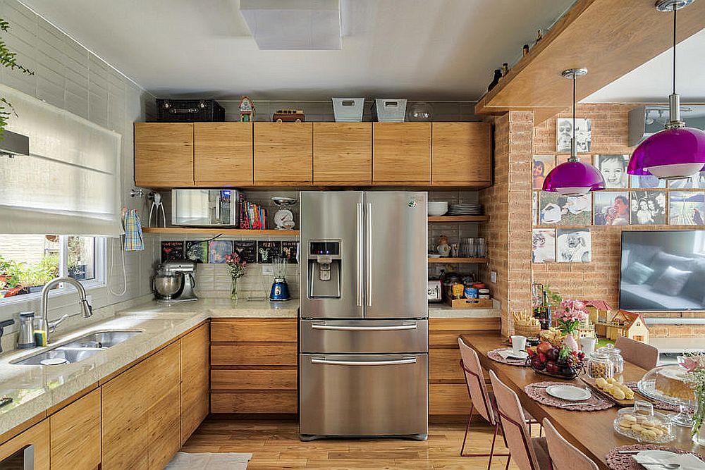 Mobilierul de bucătărie se continuă firesc perimetral, cu frigiderul în zona accesibilă, alături de masă și blat generos între plită și chiuvetă, bine iluminat natural, grație ferestrei din zonă. Fronturile din lemn ale mobilierului. Blatul ales este unul lucios, de grosime mai mare și în nuanță similară deschisă plăcilor ceramice de pe pe perete. Plăcile ceramice sunt alese sp continue vizual liniile imprimate de placare cu cărămidă.