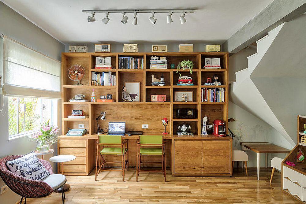 Loc de birou, bibliotecă, dar și loc de joacă pentru fetițe în cea mai liberă parte a livingului. Nu întâmplător această zonă liberă pe centrul ei se află aproape de scara interioară. Astfel, circulația către etaj nu este împiedicată. Ansamblul de mobilier este tot din lemn, continuând linia mobilierului de bucătărie și amplificând senzația de căldură, specifică unui ambient dedicat vieții de familie.