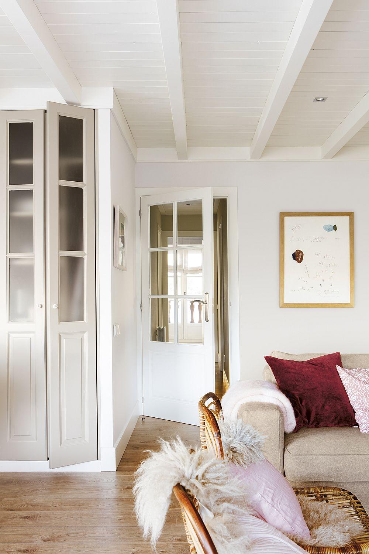 Zona de depozitare din bucătărie este completată de o nișă cu uși de tip vitrină. Dar acest spațiu ce lasă interiorul mobilierului la vedere se află la granița dintre bucătărie și living. De remarcat prezența din plin a albului și a tonurile deschise de griuri, bejuri și lemn.