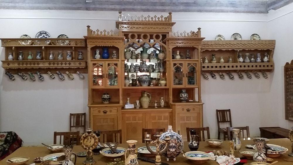 În încăperea cu divan și masă, un bufet maiestuos adăpostește o parte din colecția de ceramică.