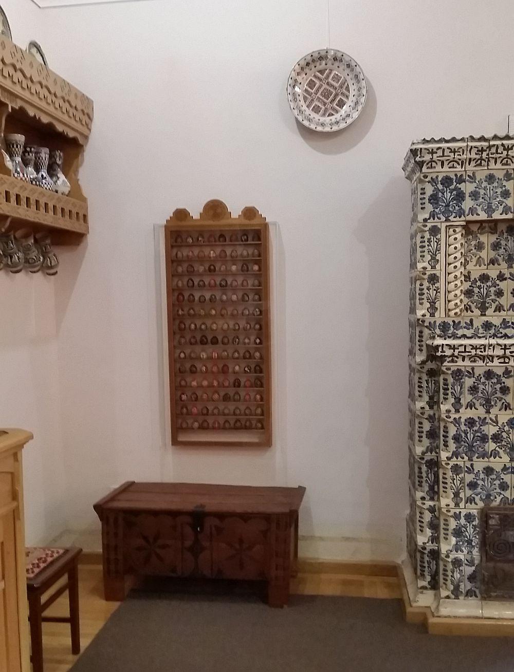 Colecție de ouă încondeiate protejate într-o casetă de lemn cu sticlă, fixată pe perete.