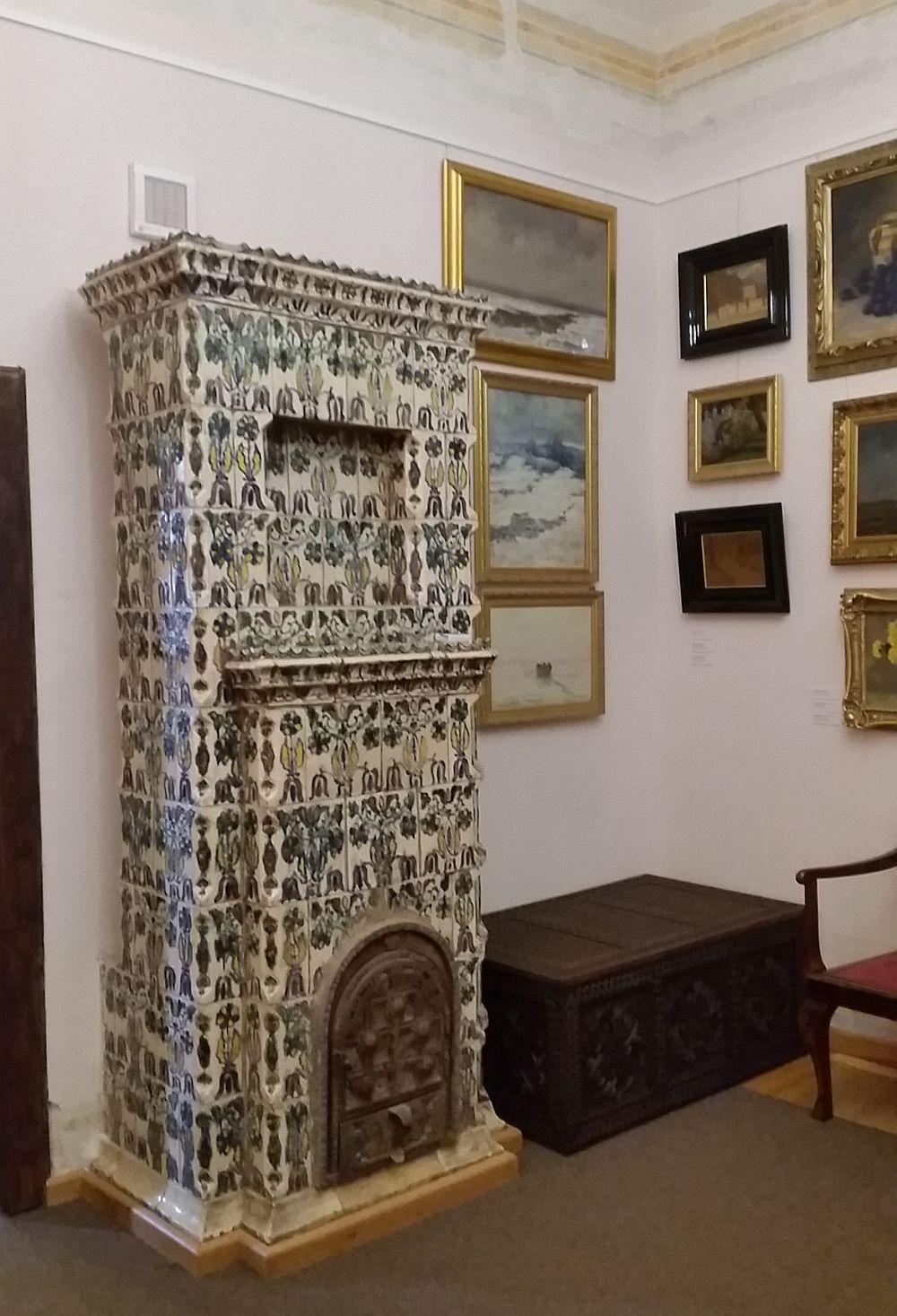 Sobă din ante camera bisericească unde există colecție de tablouri, dar și o sobă cu cahle pictate în mai multe nuanțe.