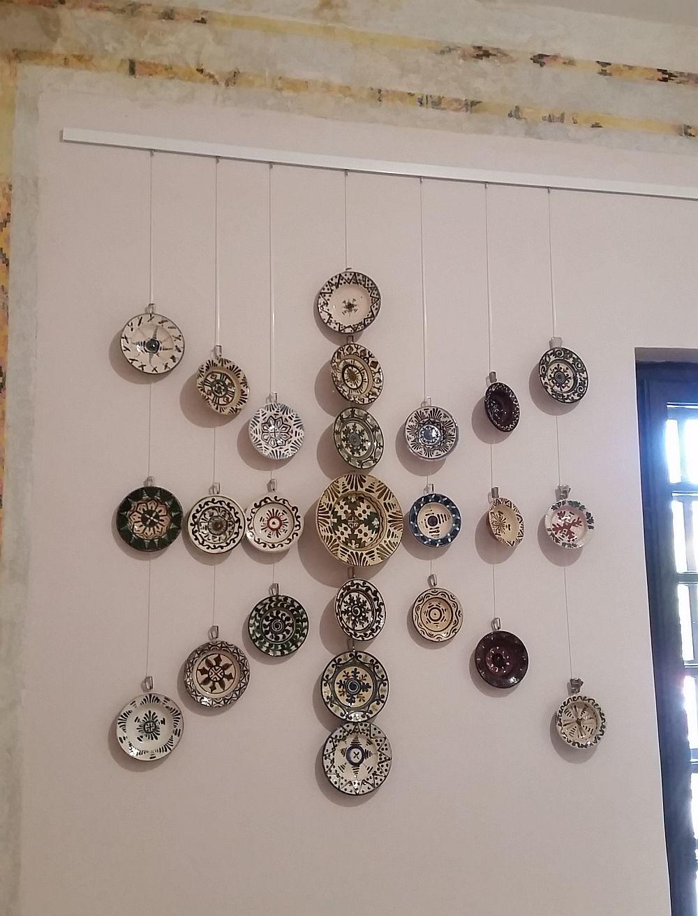 Instalație de farfurii din ceramică pe holul de la etajul Vilei Minovici. Se pot vedea și brîurile pictate sau ce s-a mai putut recupera din ele.