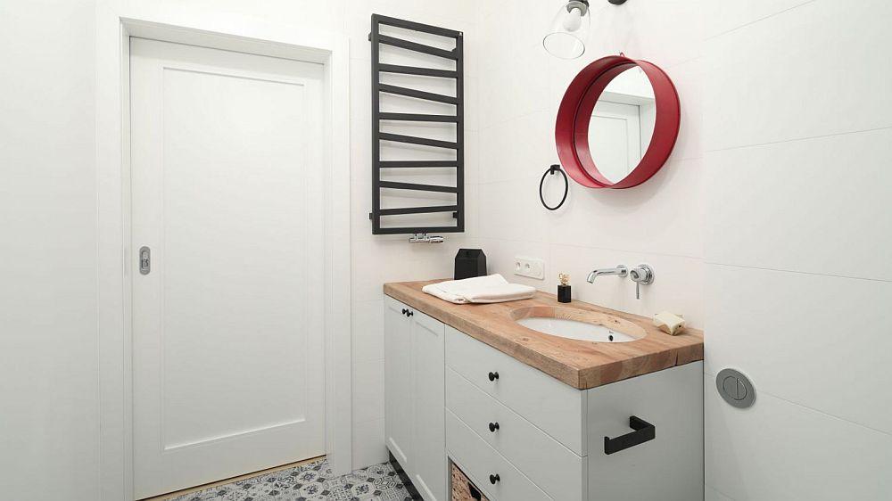 Camera de baie este mobilată și dotată cu strictul necesar, dar s-a pus accent pe designul obiectelor folosite. Mult alb, dar caloriferul iese în evidență, la fel ca și rama oglinzii.