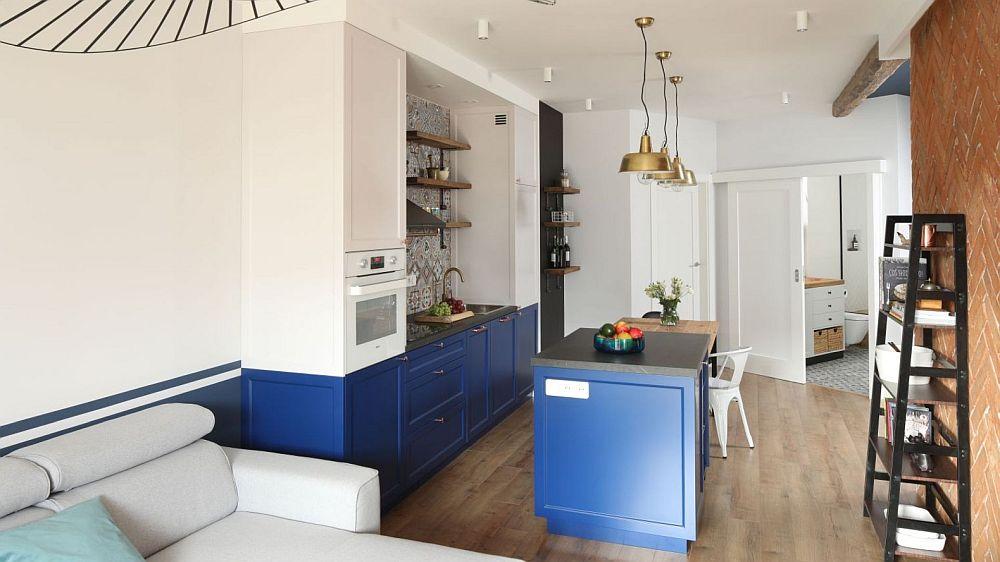 Linia corpurilor inferioare ale mobilierului de bucătărie este continuată în living prin vopsirea pereților din spatele canapelei.