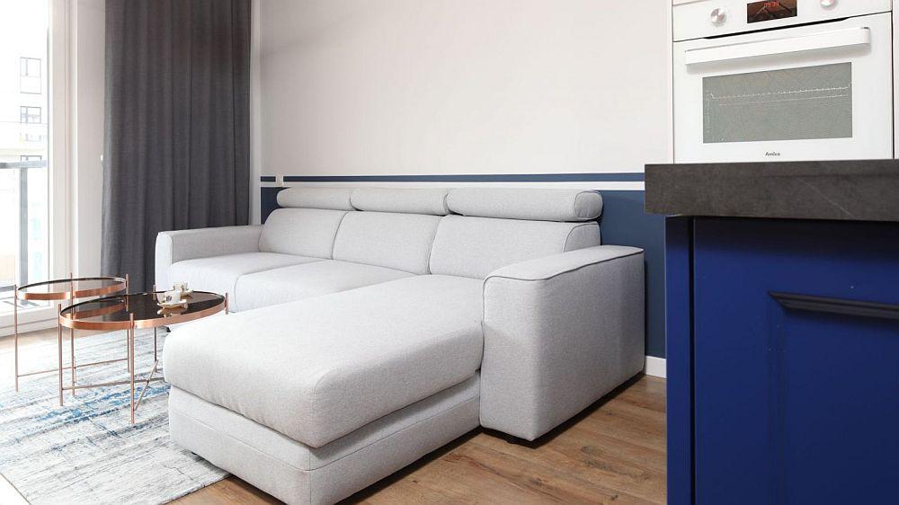 Zona de canapea este simplă, funcțională și confortabilă. Având în vedere că pe partea opusă este peretele îmbrăcat cu cărămidă, în spatele canapelei și mai sus de ea peretele a fost lăsat liber, pentru a nu încărca spațiul lung și îngust.