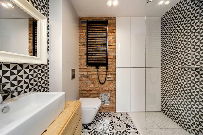 În locul căzii, tinerii soți au optat pentru un duș, marcat și prin finisaje diferite față de restul ambientului. Zona de cărămidă aparentă vine să spargă monotonia plăcilor alb-negre și să adauge un plus de textură și culoare în ambient, în completarea mobilierului din lemn.