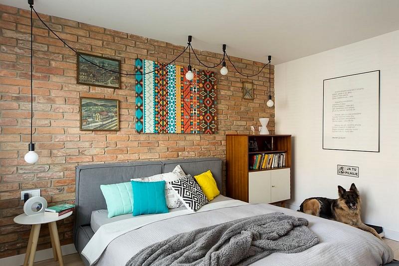 Dormitorul matrimonial are un aer puțin formal, grație peretelui de accent îmbrăcat cu cărămidă decorativă. Pe fundal acestui perete ies în evidență instalația de corpuri de iluminat, dar și tablourile colorate - accentele vsele dorite de către proprietară.
