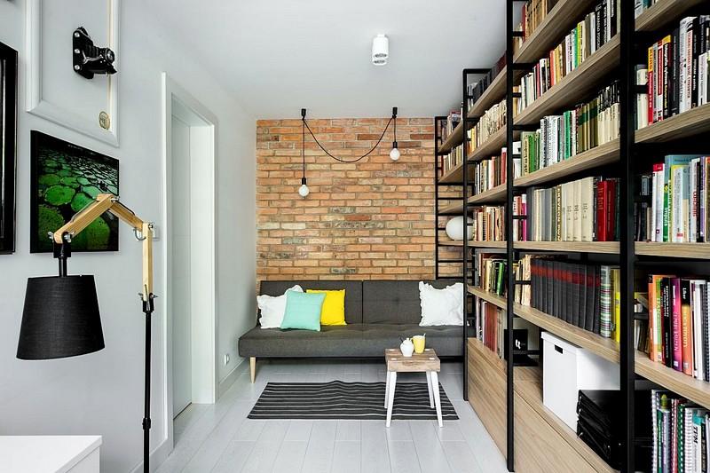 Zona de birou servește și ca încăpere pentru oaspeți, de aceea canapeaua prezentă aici este un model extensibil. Biblioteca generoasă are și spații de depozitare în partea de jos, unde corpurile au uși. Peretele de accent cu cărămidă aparentă personalizează încăperea alături de corpurile de iluminat și tablourile prezente în zona mesei de birou.