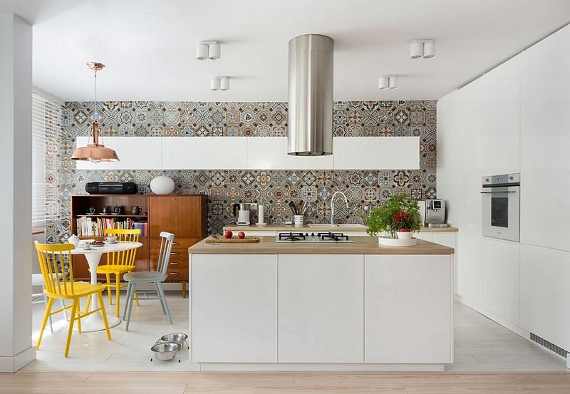 Bucătăria este foarte ordonat amenajată cu mobilă albă realizată ep comandă, fără mânere vizibile, ci echipată cu sisteme push. Un perete întreg din bucătărie a fost placat cu faiantă de tip patchwork care aduce un plus de culoare și veselie în ambient. Aspectul plăcilor ceramice este similar unui tapet. Pe acest fundal un corp lung de mobilă suspendat se citește clar prin contrast, iar zona mesei este marcată printr-un design vintage.