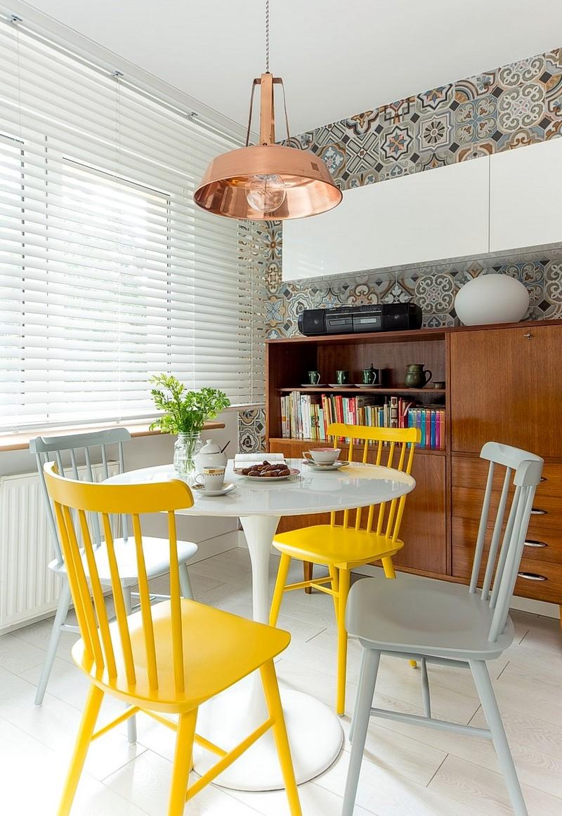 Locul de luat masa este nota veselă din ambientul bucătăriei. Pe fundalul deschis al pardoselii și cu mult alb în jur pe suprafețe mari, scaunele galbene sunt foarte vizibile și ei conferă din start o notă solară locului. Este un truct binevenit în orice ambient ca petele de culoare să fie prezente prin obiecte care se pot înlocuit ușor, cu ar fi scaunele.