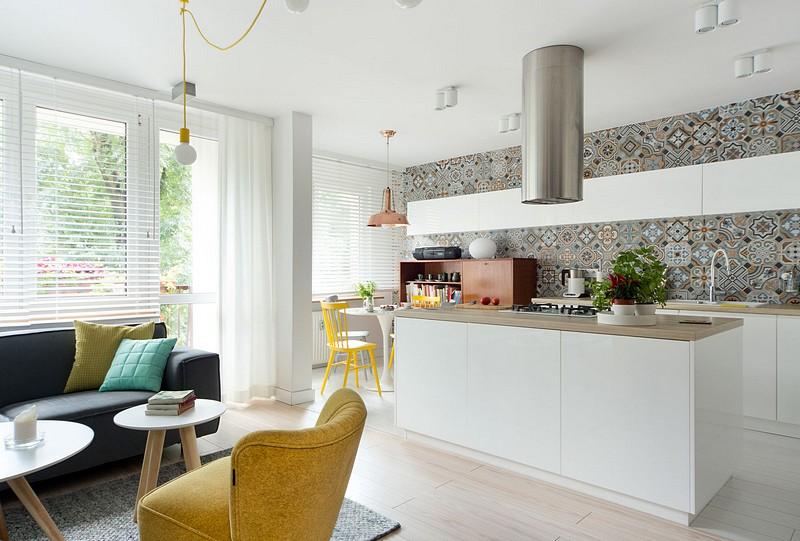 Separarea dintre living și bucătărie s-a făcut prin intermediul mesei insulă. Deasupra acesteia este instalată hota, al cărui burlan de evacuare este mascat în plafonul fals. Prezența mesei insulă ascunde vizual o mare parte din pardoseala bucătăriei, care este diferită de cea a livingului, dar montată similar. În living este parchet, iar în bucătărie este gresie cu aspect de parchet.