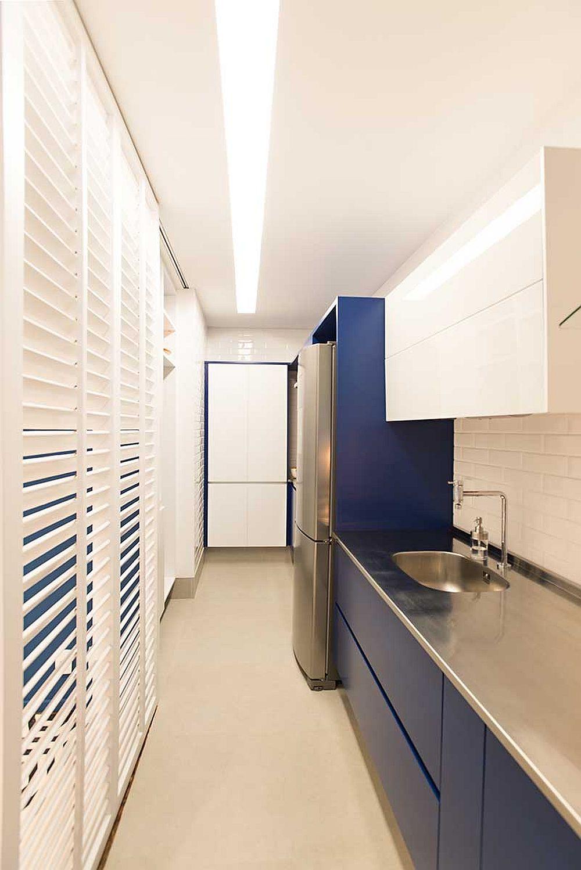 Bucătăria este amenajată într-un spațiu lung și îngust, dar totul bine organizat, cu loc de blat generos între chiuvetă și plită.