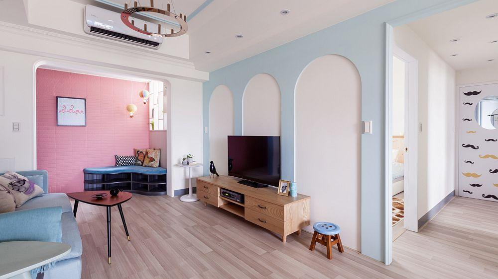 Peretele din zona unde este situat televizorul a fost jucăuș decorat cu arcade colorate. Acest desen aduce un plus de feminitate, dar te trimite cu gândul și la parcurile de distracție pentru copii. Mobila fiind joasă, prin acest artificiu decorativ designerii au subliniat înălțimea spațiului și au corelat arcada ciudată ce separă holul cu spațiul livingului. După zona de tv se poate vedea holul către dormitoare și baie, ușa băii fiind personalizată cu desene jucăușe.