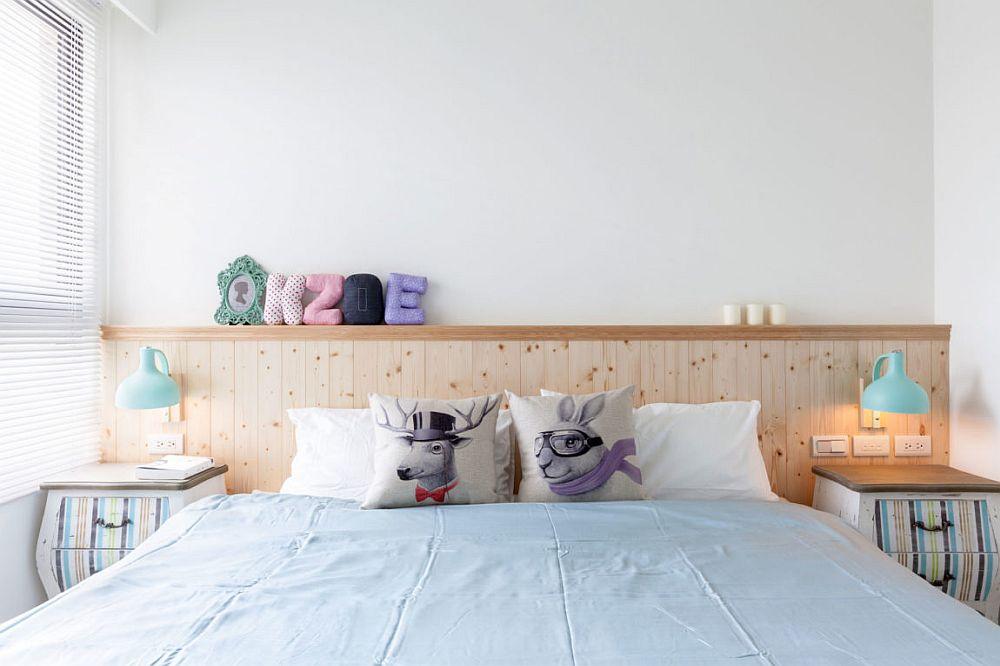 Tăblia patului depășește cadrul saltelei, marcând și locul noptierelor, punctate de corpuri de iluminat. Culorile sunt prezente aici prin mici decorațiuni și intervenții decorative la nivelul noptierelor.