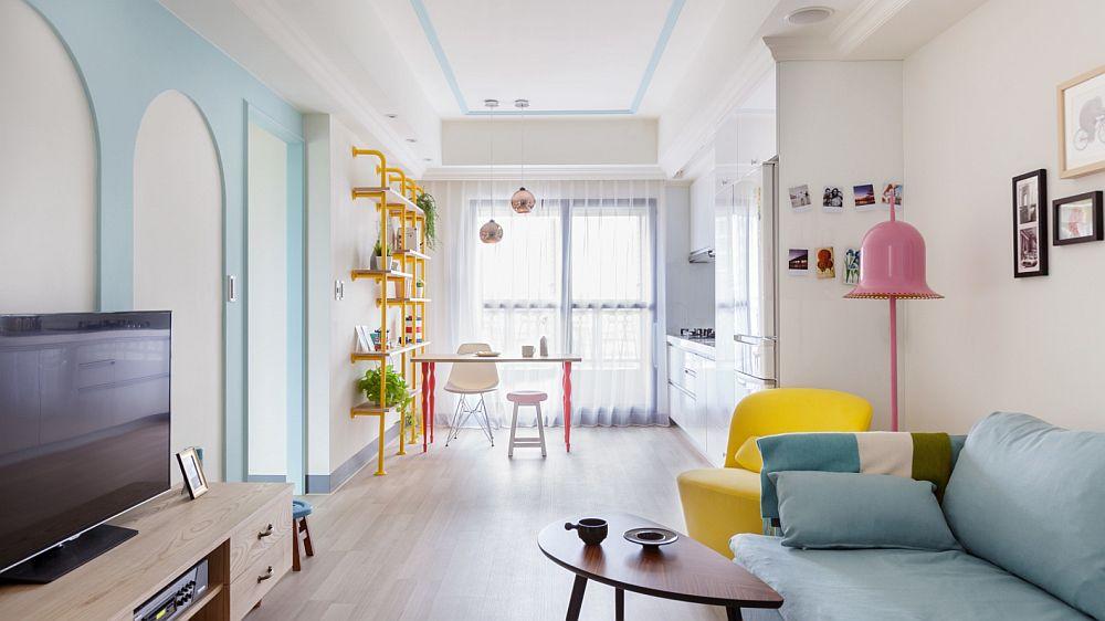 Spațiul zonei de zi este unul lung și îngust. Pentru ca această senzație de lungime să fie temperată, designerii au avut în vedere ca suprafața ferestrelor să nu fie blocată cu mobilier masiv. Ca atare totul este dispus perimetral, iar în fața ferestrei masa existentă este sculpturală, ușoară, lăsând lumina să pătrundă către centrul camerei. Culorile sunt prezente în acest spațiu într-o combinație plăcută. Albastrul relaxant este pe suprafețele cele mai mari, apoi rozul ca ccent la fel și galbenul. Dar din nou cele mai mari suprafețe sunt albe.